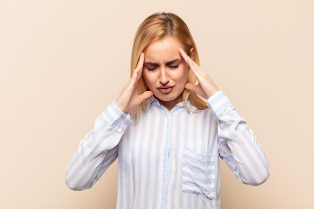 ストレスと欲求不満を見て、頭痛でプレッシャーの下で働いて、問題に悩まされている若いブロンドの女性