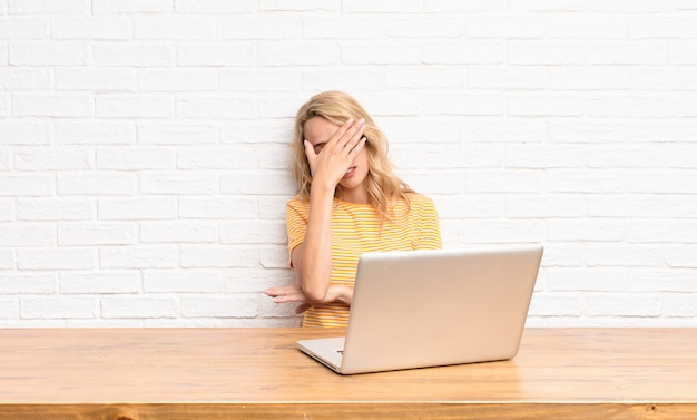 Young blonde woman looking stressed, ashamed or upset, with a headache, covering face with hand using a laptop