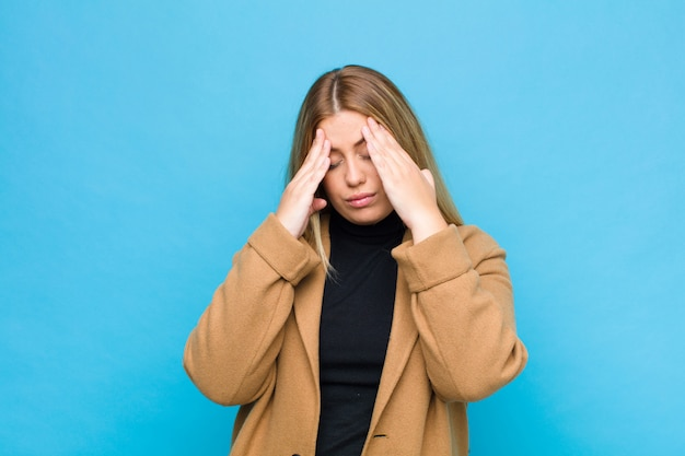 Young blonde woman looking stressed and frustrated, working under pressure with a headache and troubled with problems over wall