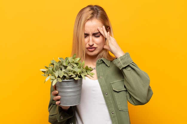 Young blonde woman looking stressed and frustrated, working under pressure with a headache and troubled with problems