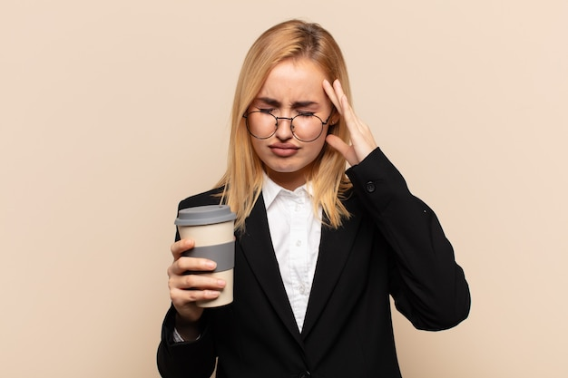 Young blonde woman looking stressed and frustrated, working under pressure with a headache