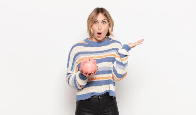Young blonde woman looking surprised and shocked, with jaw dropped holding an object with an open hand on the side