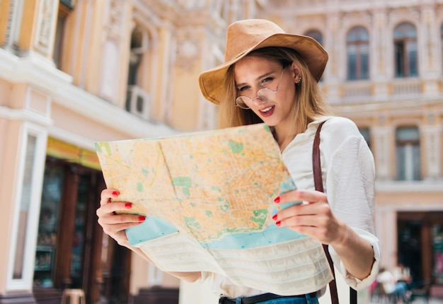 市内地図を探している若いブロンドの女性