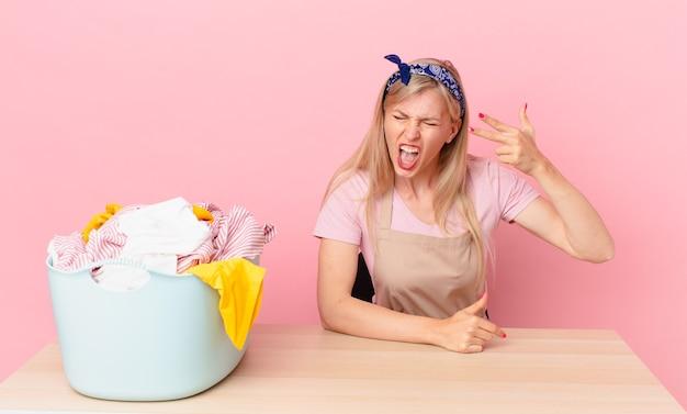 Молодая белокурая женщина, выглядящая несчастной и подчеркнутой, жест самоубийства, делая знак пистолета. концепция стирки одежды