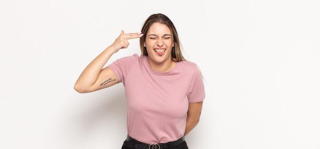 불행하고 스트레스를받는 젊은 금발의 여자, 머리를 가리키는 손으로 총 기호를 만드는 자살 제스처