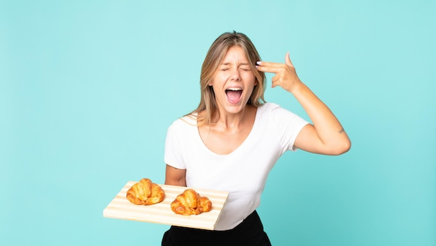 Young blonde woman looking unhappy and stressed, suicide gesture making gun sign and holding a croissant tray
