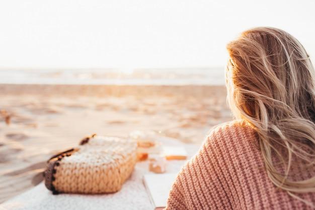 ビーチまたは海で一人で横になって、水平線を見て若いブロンドの女性。暖かいセーターを着た女性。トーン。顔は見えません。