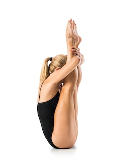 Young blonde woman in maillot practicing rhythmic gymnastics
