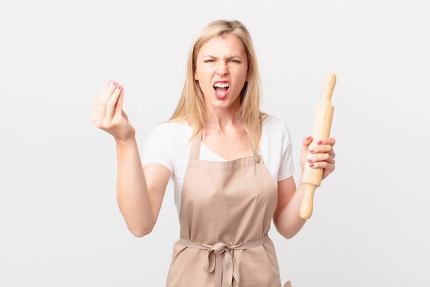 Young blonde woman making capice or money gesture, telling you to pay. baker concept