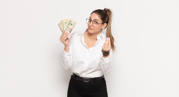 Young blonde woman making capice or money gesture, telling you to pay your debts!
