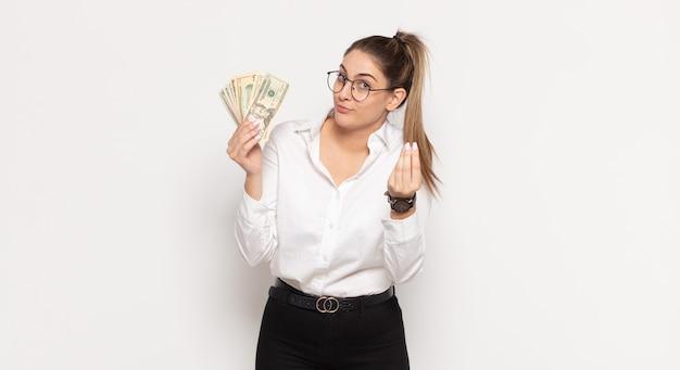 あなたの借金を支払うようにあなたに言って、capiceまたはお金のジェスチャーをしている若いブロンドの女性!
