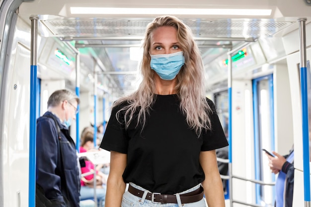 Young blonde woman in a mask in a subway wagon