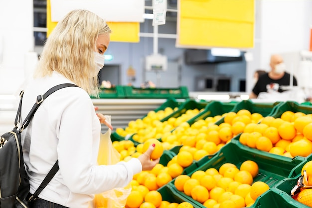 A young blonde woman in a medical mask buys fruits in a supermarket
