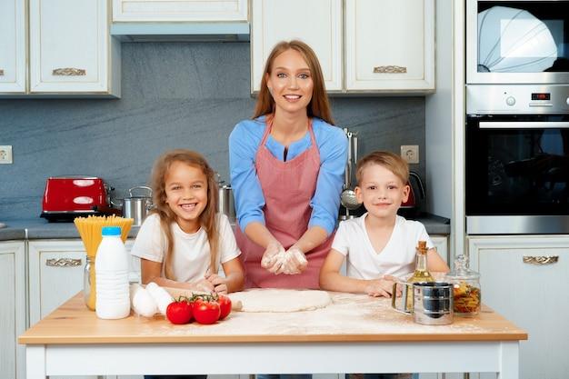 Молодая блондинка, мать и ее дети веселятся во время приготовления теста