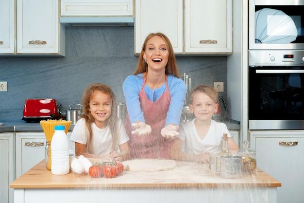 若いブロンドの女性、母と彼女の子供たちが生地を調理しながら楽しんで