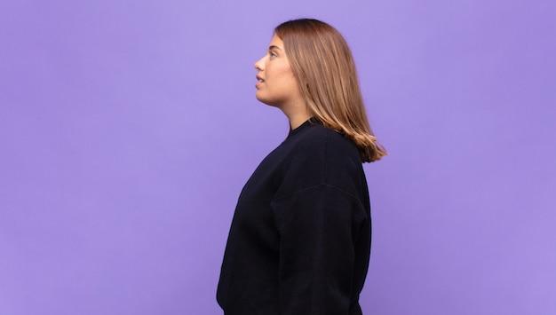 프로필보기에 젊은 금발의 여자는 앞서 공간을 복사하려고 생각, 상상 또는 공상
