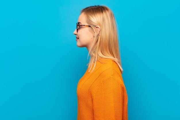 Молодая блондинка в профиль смотрит, чтобы скопировать пространство впереди, думает, воображает или мечтает
