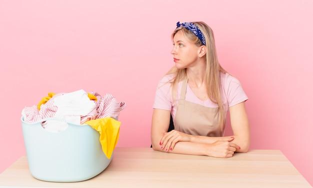 Молодая блондинка женщина на взгляде профиля мышления, воображения или мечтания. концепция стирки одежды