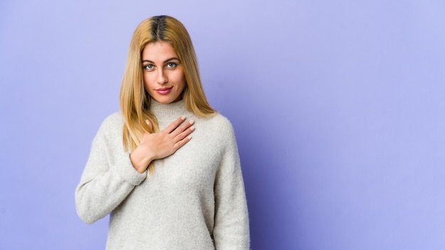 Молодая белокурая женщина на фиолетовой стене принимая присягу, кладя руку на комод.