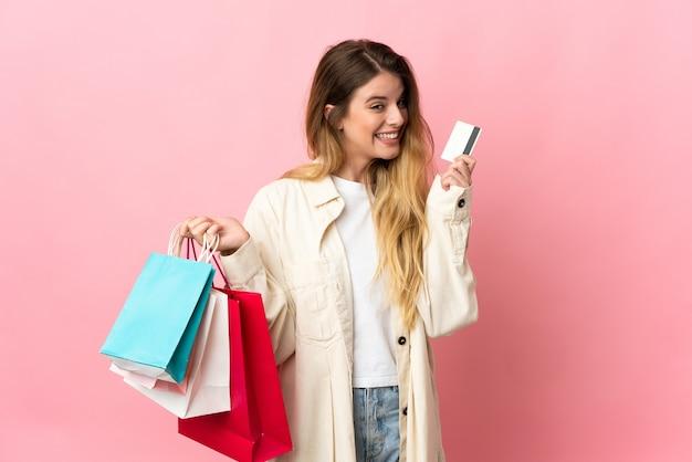 Молодая блондинка женщина на фоне холдинг сумки и кредитная карта