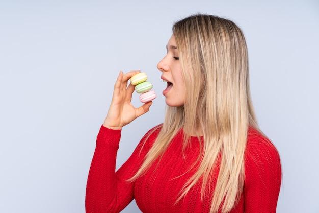 Молодая белокурая женщина над голубым держа красочные французские macarons и есть его