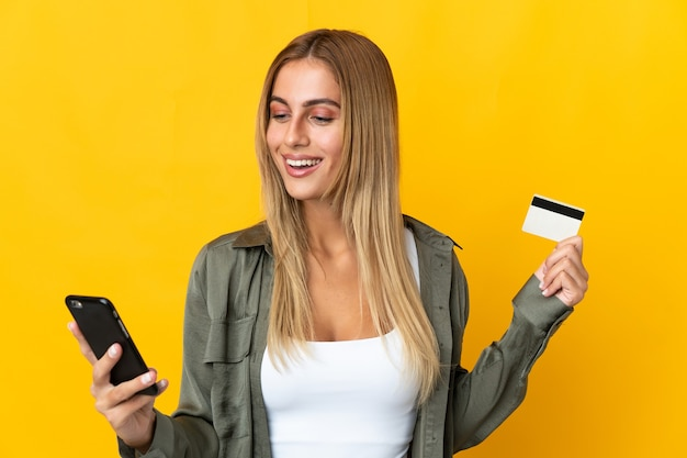 Молодая блондинка за покупкой с помощью мобильного телефона с помощью кредитной карты