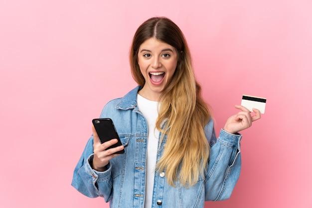 Молодая блондинка женщина на изолированном фоне покупает с мобильного телефона и держит кредитную карту с удивленным выражением лица