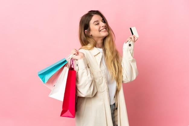 Молодая блондинка женщина на изолированном фоне держит сумки и кредитную карту