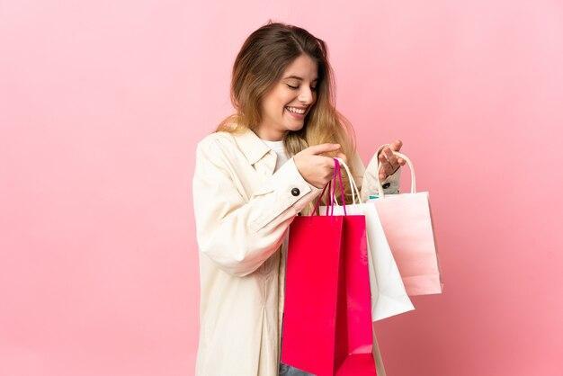 쇼핑백을 들고 내부를 찾고 격리 된 배경 위에 젊은 금발의 여자