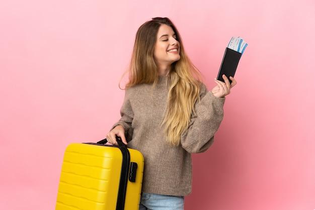 スーツケースとパスポートと休暇で孤立した背景上の若いブロンドの女性