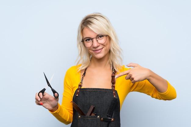 Молодая белокурая женщина над изолированной предпосылкой с платьем парикмахера или парикмахера и указывать его
