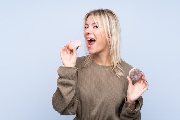 Молодая белокурая женщина над изолированной голубой стеной есть пончик