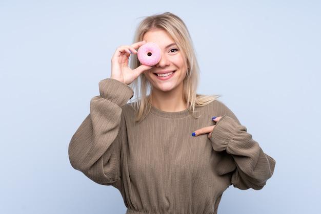 Молодая белокурая женщина над изолированной голубой стеной держа пончик и счастливый