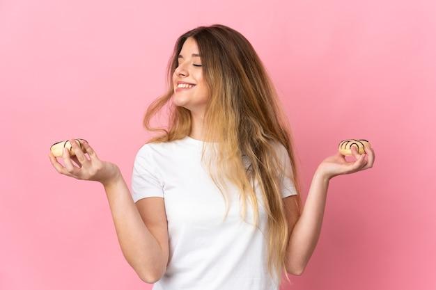 幸せな表情で孤立した保持ドーナツ上の若いブロンドの女性
