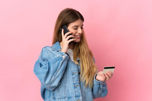 Молодая блондинка женщина над изолированным пространством покупает мобильный телефон с помощью кредитной карты
