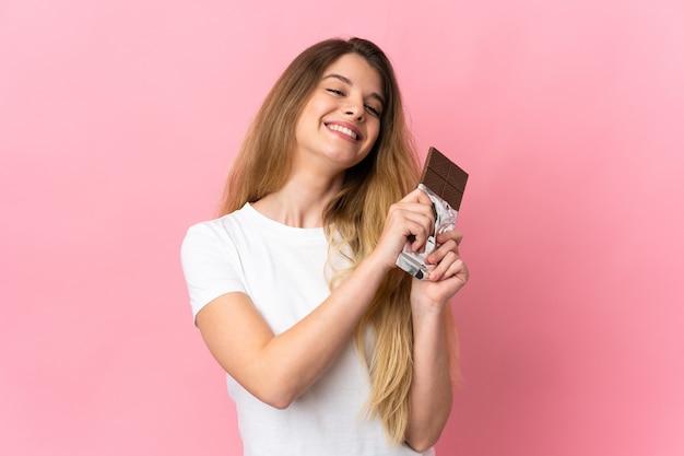 チョコレートタブレットを取り、幸せな孤立した若いブロンドの女性