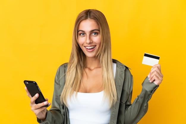 Молодая белокурая женщина над изолированной стеной покупает с мобильного телефона и держит кредитную карту с удивленным выражением лица