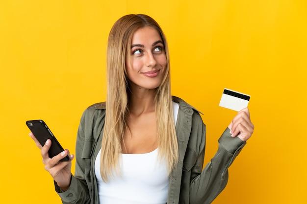 Молодая блондинка женщина над изолированной стеной покупает мобильный телефон с помощью кредитной карты, думая