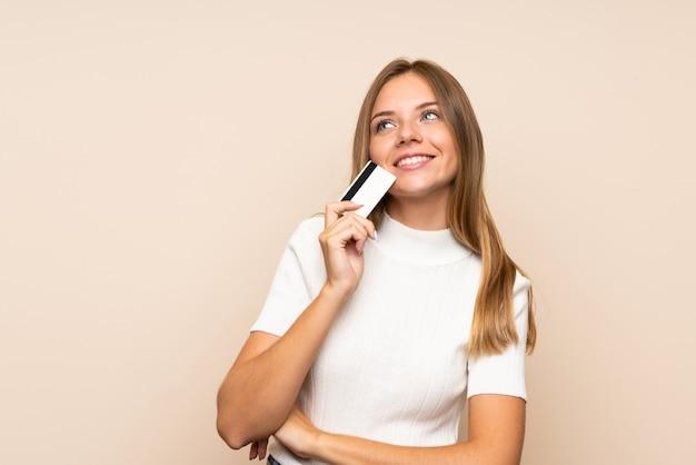Молодая белокурая женщина над изолированной стеной держа кредитную карточку