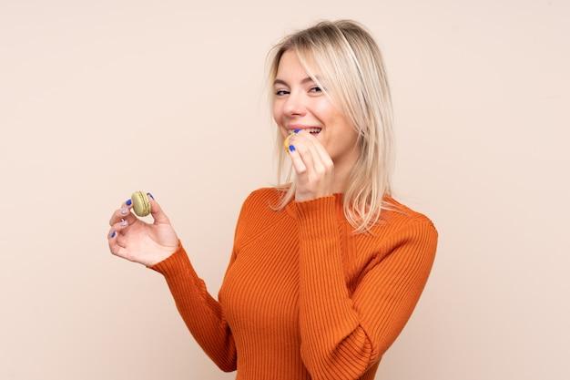 Молодая белокурая женщина над изолированной стеной держа красочные французские macarons и есть его