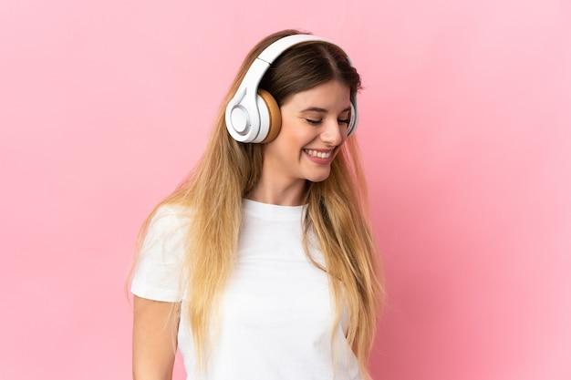 Молодая блондинка женщина над изолированной стеной, слушая музыку