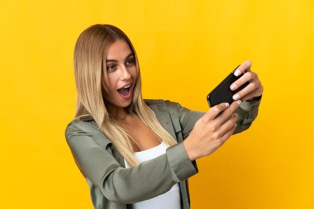 Молодая блондинка женщина над изолированной стеной играет с мобильным телефоном