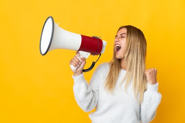Молодая блондинка над изолированной стеной кричит в мегафон, чтобы объявить что-то в боковом положении