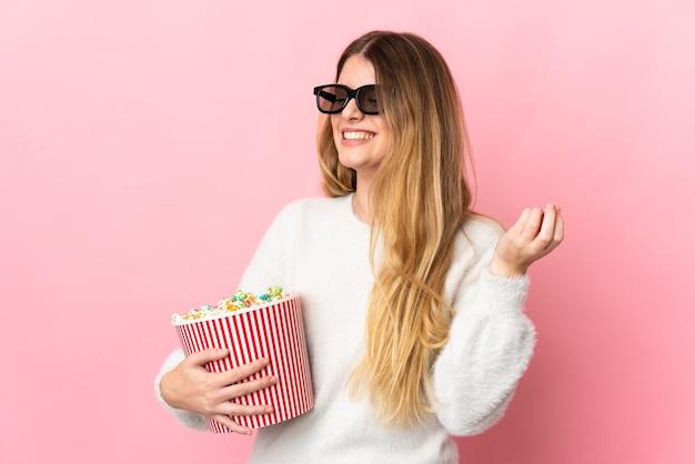 3dメガネと孤立した壁の上の若いブロンドの女性と側面を見ながらポップコーンの大きなバケツを保持します。