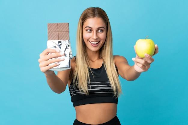 Молодая блондинка берет шоколадную таблетку в одну руку и яблоко в другой