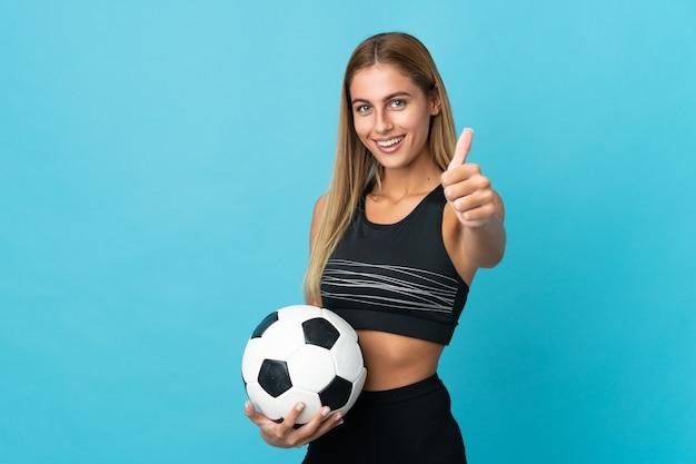 サッカーボールと親指を上にして若いブロンドの女性