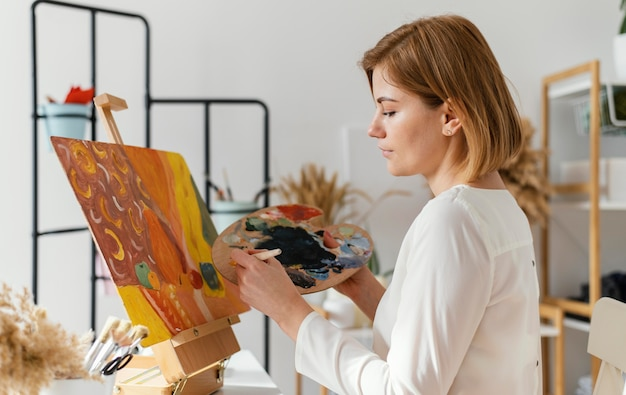アクリルで絵を描く若いブロンドの女性