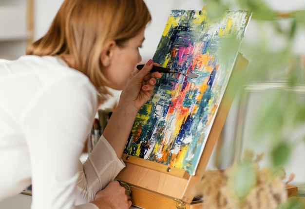 Young blonde woman painting with acrylics