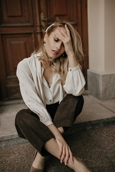 Young blonde woman in pearl necklace, white stylish blouse and brown pants sits on floor near wooden door outside