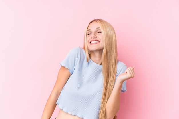 Young blonde woman on pink background dancing and having fun.